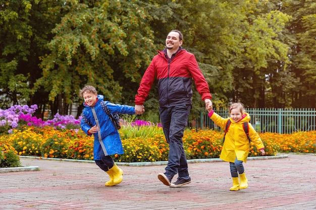 I bambini felici ridono, si precipitano e corrono a scuola vestiti con impermeabili Foto Premium