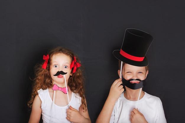 I bambini gemelli carini tengono baffi e barba di carnevale Foto Premium