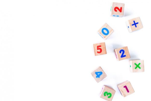 I bambini gioca i cuccioli di legno con i numeri su fondo bianco. lo sviluppo di blocchi di legno. giocattoli naturali ed ecologici per bambini. vista dall'alto. disteso. copia spazio. Foto Premium