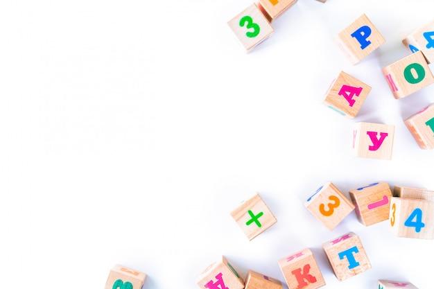 I bambini gioca i cuccioli di legno con le lettere e numeri su fondo bianco. lo sviluppo di blocchi di legno. giocattoli naturali ed ecologici per bambini. vista dall'alto. disteso. copia spazio. Foto Premium