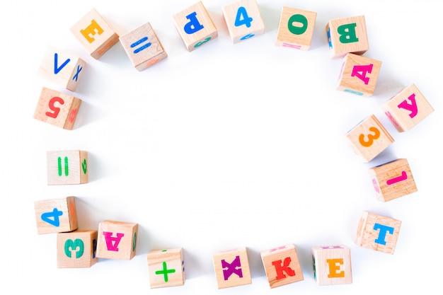 I bambini gioca i cuccioli di legno con le lettere e numeri su fondo bianco. telaio dallo sviluppo di blocchi di legno. giocattoli naturali ed ecologici per bambini. vista dall'alto. disteso. copia spazio. Foto Premium