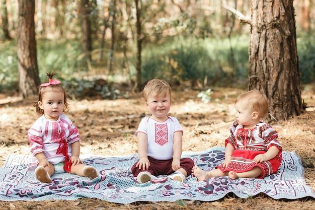 I bambini in abiti tradizionali ucraini giocano nella foresta in raggio di sole. ragazzo e due ragazze Foto Gratuite