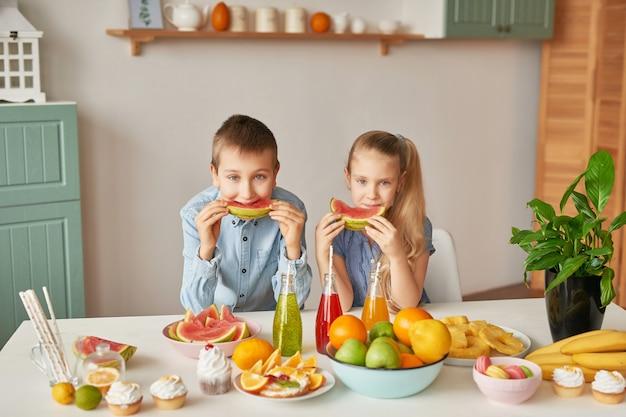 I bambini mangiano le fette di anguria in cucina Foto Premium
