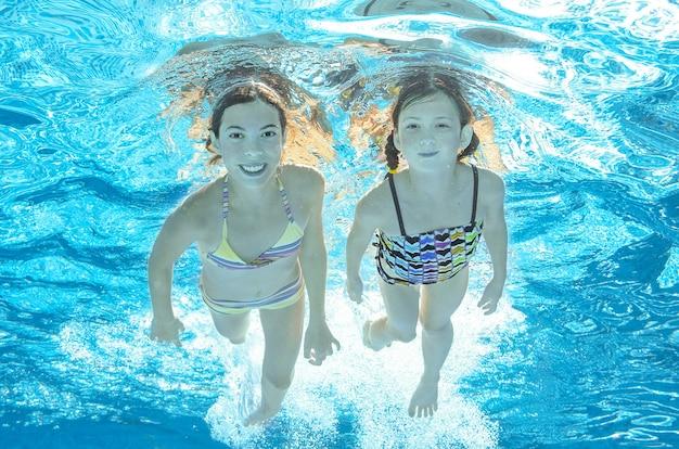 I bambini nuotano sott'acqua in piscina, le ragazze attive felici si divertono sott'acqua Foto Premium