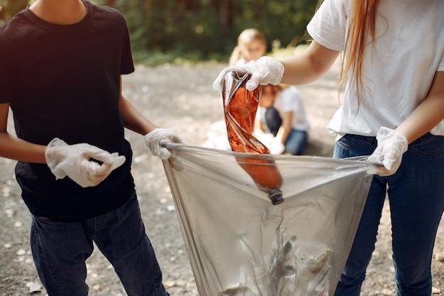 I bambini raccolgono immondizia nei sacchetti di immondizia nel parco Foto Gratuite