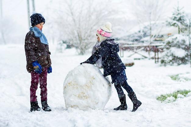 I bambini ragazzo e ragazza all'aperto in inverno nevoso stanno facendo un grande pupazzo di neve Foto Premium