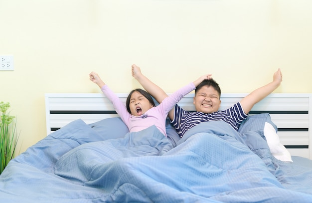 I bambini si allungano nel letto dopo essersi svegliati, Foto Premium