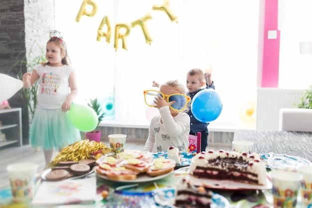 Tavolo Compleanno Bambini : I bambini si avvicinano al tavolo per la festa di compleanno