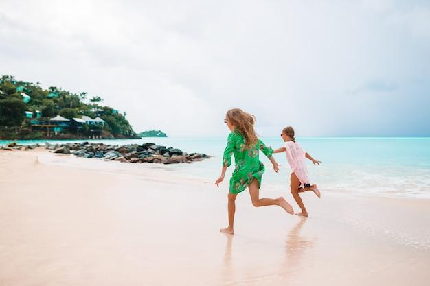 I bambini si divertono molto sulla spiaggia tropicale giocando insieme Foto Premium