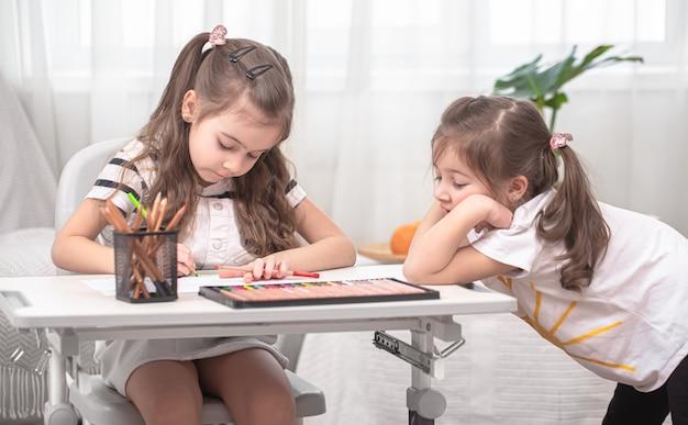 I bambini si siedono al tavolo e fanno i compiti. il bambino impara a casa. scuola a casa. Foto Gratuite
