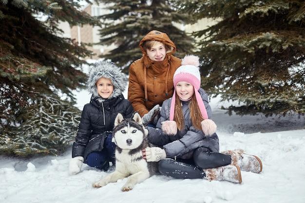 I bambini si siedono sulla neve e accarezzarono il cane husky. i bambini escono e giocano con il cane husky in inverno. camminare nel parco Foto Premium
