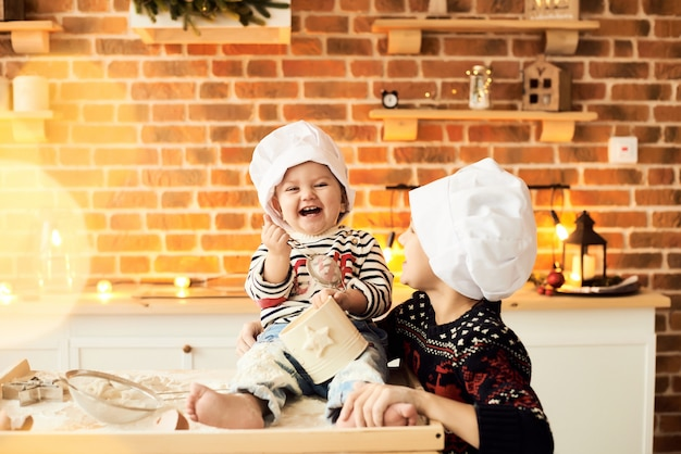 I bambini sono cucinati e giocati con farina e impasto in cucina Foto Premium