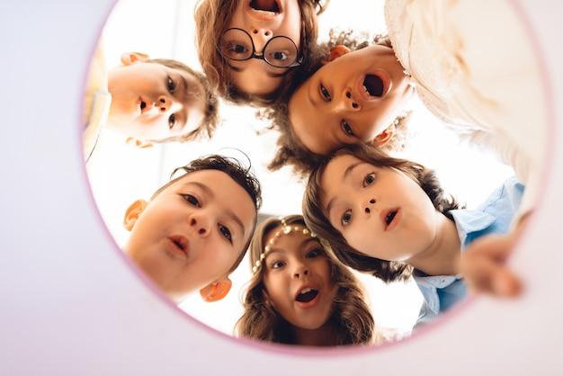 I bambini sorpresi guardano insieme nel contenitore di regalo rotondo. Foto Premium