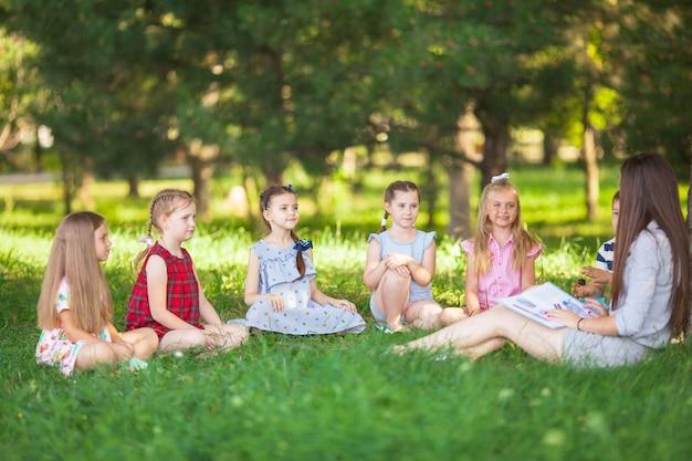 I bambini tengono una lezione con l'insegnante nel parco su un prato verde. Foto Premium