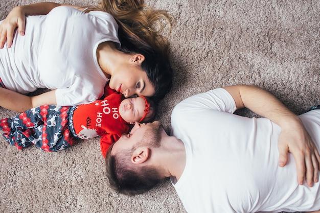 I bei genitori con la figlia sdraiata sul pavimento Foto Gratuite
