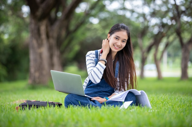 I bei libri asiatici della tenuta della studentessa e sorridere e l'apprendimento e l'educazione sul parco di estate per si rilassano il tempo Foto Premium