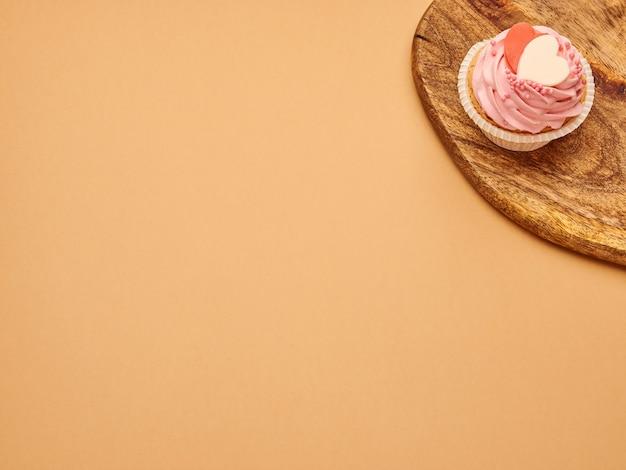 I bigné rosa agglutina con i cuori su un bordo di legno della cucina su un fondo marrone beige Foto Premium