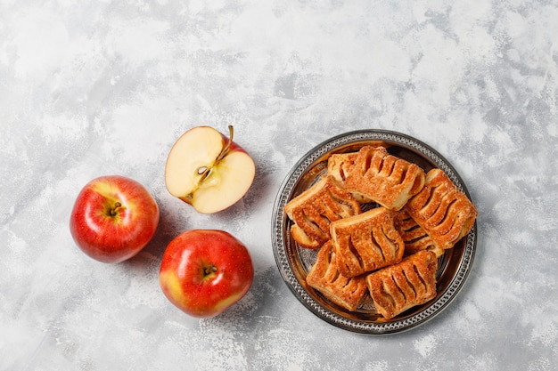 I biscotti della pasta sfoglia hanno riempito di marmellata di mele e mele rosse fresche su calcestruzzo leggero Foto Gratuite