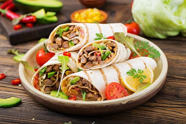I burritos si avvolgono con manzo e verdure su un fondo di legno. burrito di manzo, foo messicano Foto Premium
