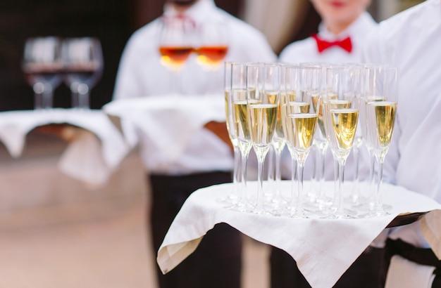 I camerieri accolgono gli ospiti con bevande alcoliche. champagne, vino rosso, vino bianco su vassoi. Foto Premium