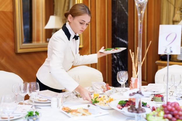 I camerieri apparecchiano i tavoli nel ristorante per il banchetto Foto Premium