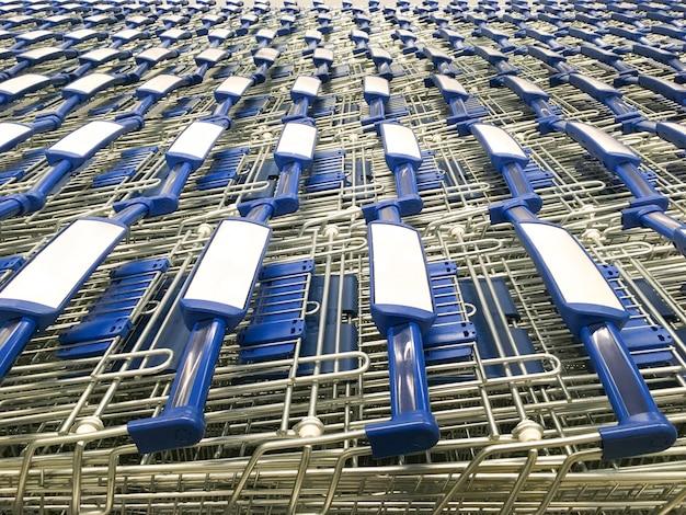 I carrelli della spesa con maniglie blu sono parcheggiati di fronte al supermercato Foto Premium