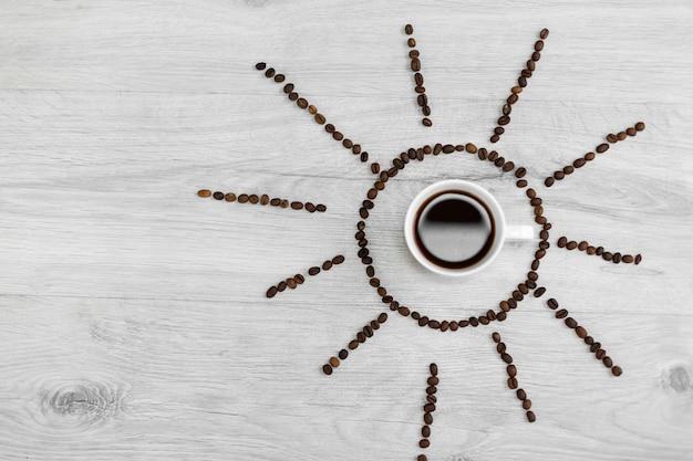 I chicchi di caffè hanno piegato sotto forma di sole su un fondo di legno Foto Premium