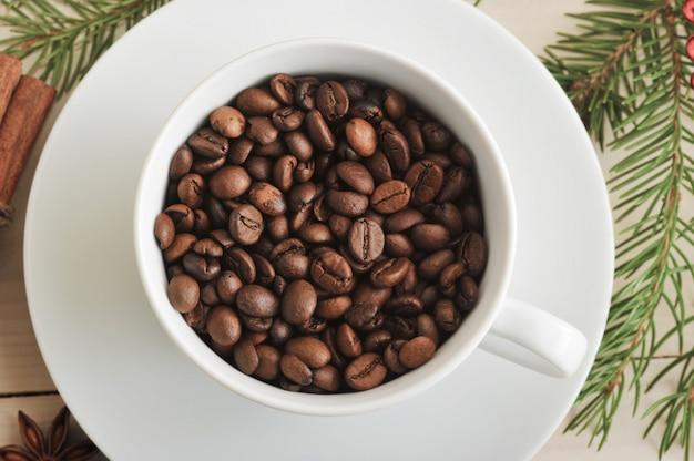 I chicchi di caffè interi vengono versati in una tazza di caffè Foto Premium