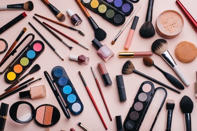 I cosmetici e il trucco delle donne hanno messo su fondo rosa. vista dall'alto Foto Premium