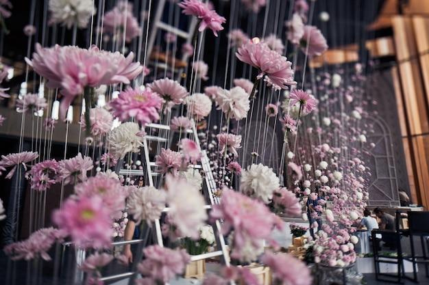 I crisantemi rosa appendono ai fili dal soffitto nella sala per la cena Foto Gratuite