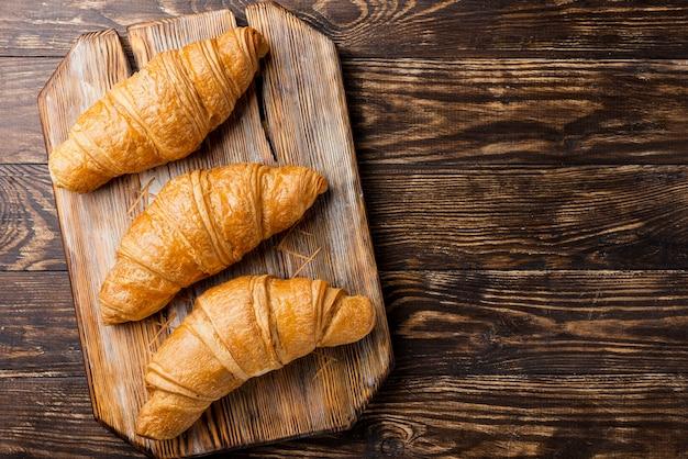 I croissant al forno deliziosi di vista superiore sul bordo di legno e copiano lo spazio Foto Gratuite