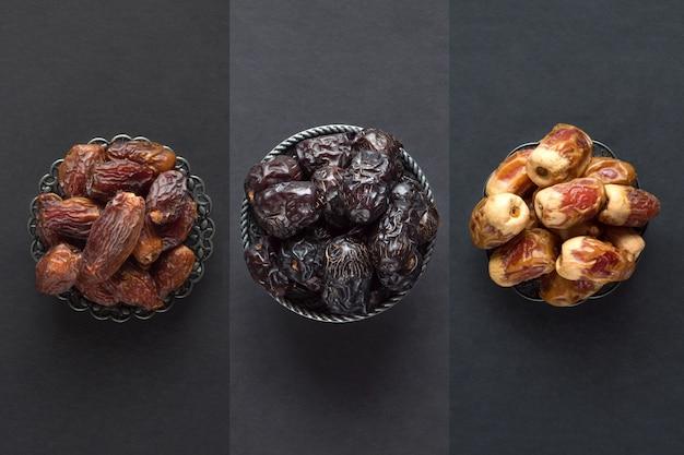 I datteri sauditi frutti sono disposti su un tavolo scuro. Foto Premium