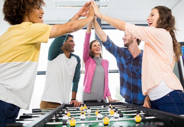 I dirigenti danno il cinque mentre giocano a calcio balilla Foto Premium