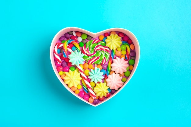 I dolci al cioccolato mix si trovano a forma di scatola regalo di cuore su sfondo colorato Foto Premium
