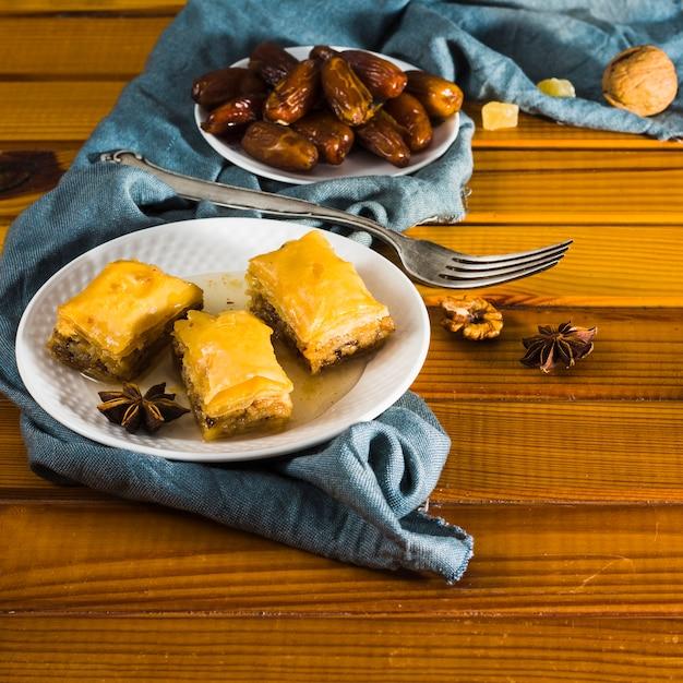 I dolci orientali con le date fruttificano sul piatto sul tavolo Foto Gratuite