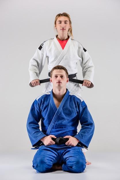 I due judoka combattenti in posa sul grigio Foto Gratuite