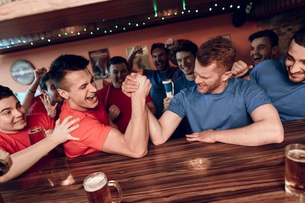 I fan della squadra blu e rossa armano il wrestling alla barra di sport Foto Premium