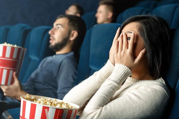 I film horror sono per i più coraggiosi. colpo del primo piano di una ragazza spaventata che la chiude occhi con le sue mani che guardano film spaventoso nel cinema Foto Premium