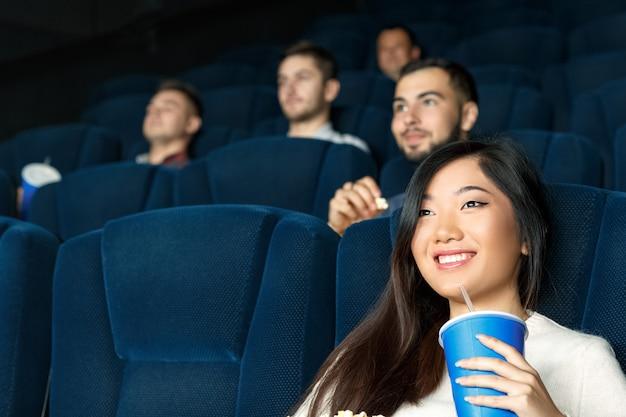 I film oggi. chiuda sul colpo di angolo basso di bella femmina asiatica che sorride mentre guardano i film Foto Premium