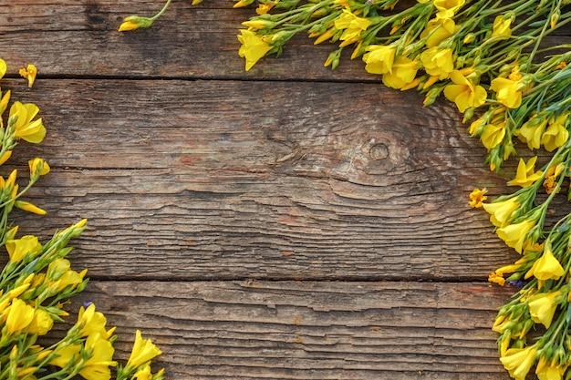 I fiori gialli sono incorniciati su un fondo di legno, su una bella molla e su un fondo festivo. Foto Premium