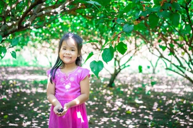 I frutti di gelso nelle mani della bambina in giardino Foto Premium