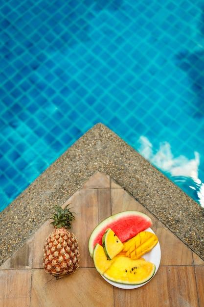 I frutti tropicali succosi hanno messo al bordo dello stagno con acqua blu di cristallo. riposo weekend di lusso. Foto Premium