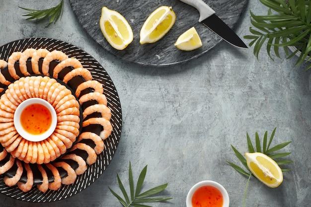 I gamberi piccante di limone e aglio sono serviti su un piatto scuro con limoni e salsa di peperoncino dolce, piatto su sfondo scuro Foto Premium