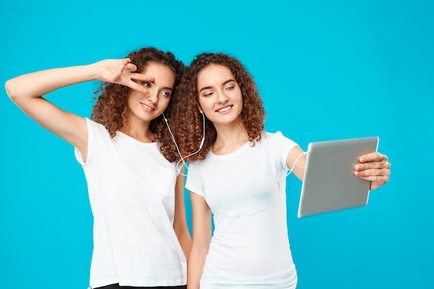 I gemelli di due womans che fanno selfie sulla compressa sopra il blu. Foto Gratuite