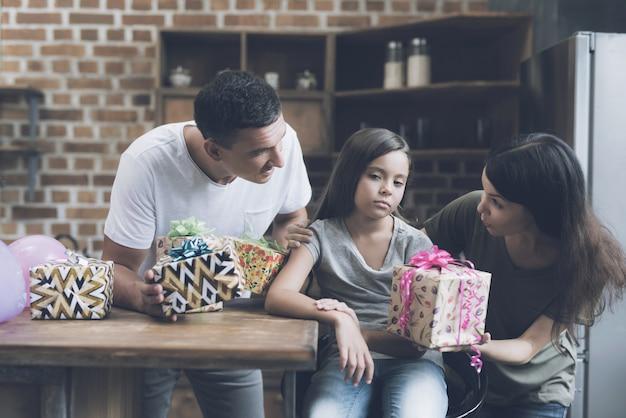 I genitori sorridono alla ragazza e cercano di darle regali Foto Premium