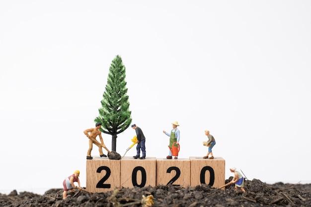 I giardinieri si prendono cura di un albero sul blocco di legno numero 2020 Foto Premium