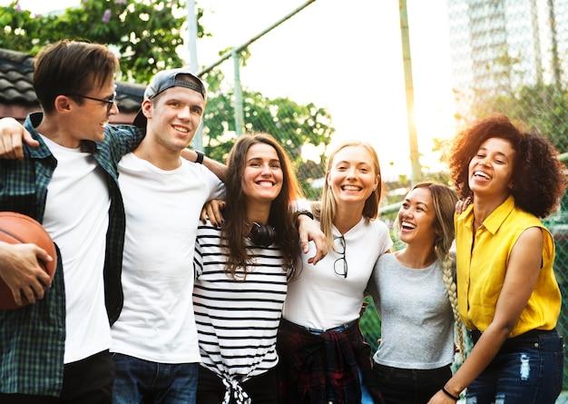 I giovani amici adulti felici sorridenti armeggia intorno all'amicizia della spalla all'aperto ed al concetto del collegamento Foto Gratuite