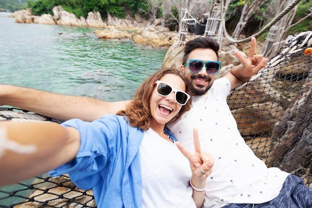 I giovani bei amici sorridenti felici felici dell'uomo e della donna delle coppie su un'amaca sulla vacanza fa il selfie su uno smartphone contro del mare Foto Premium