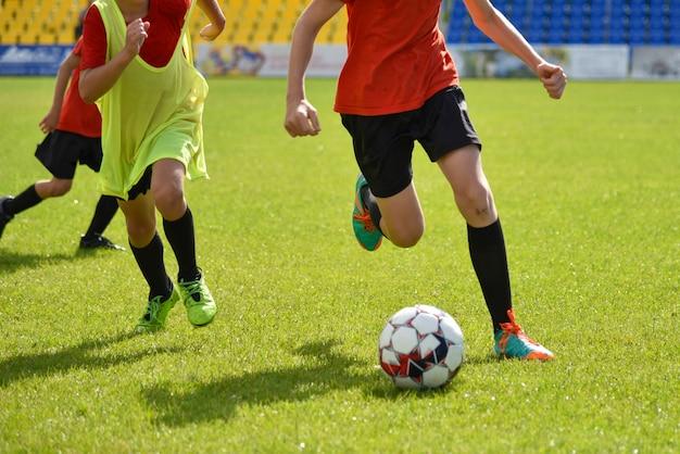I giovani calciatori giocano a calcio allo stadio Foto Premium