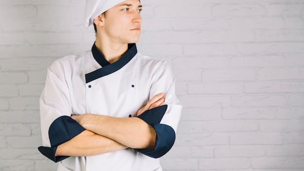 I giovani cucinano in braccia bianche dell'incrocio sul petto Foto Gratuite